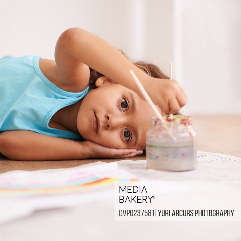 Portrait of a little girl lying on the floor by the picture she painted