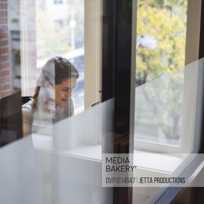 Business woman viewed working through window