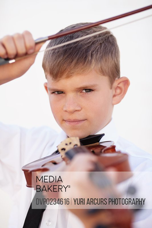 Musical young boy holding up his violin