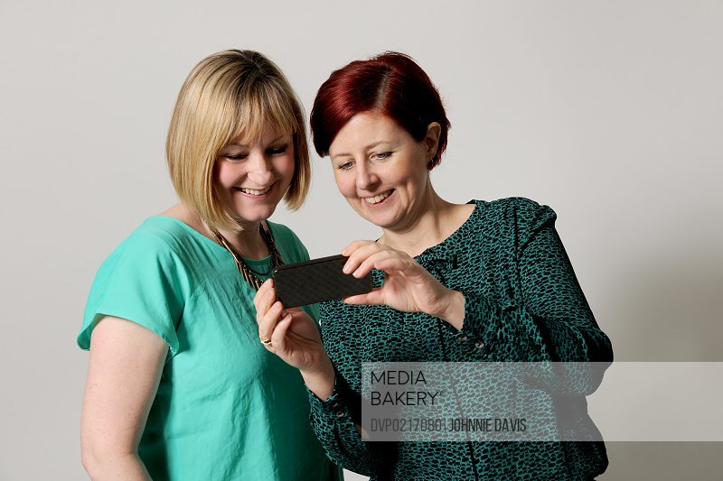 mature girlfriends looking at phone laughing