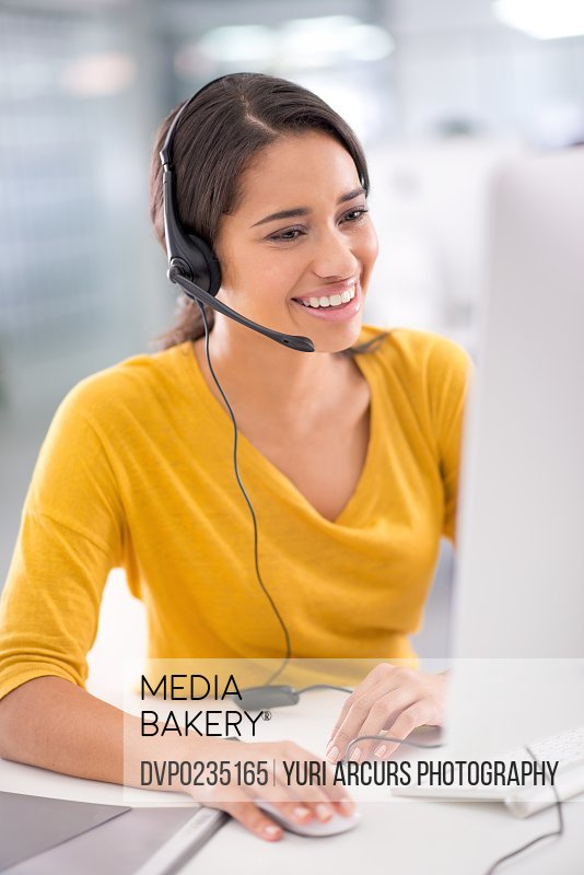 Shot of a young customer service representative wearing a headset while sitting by her computer