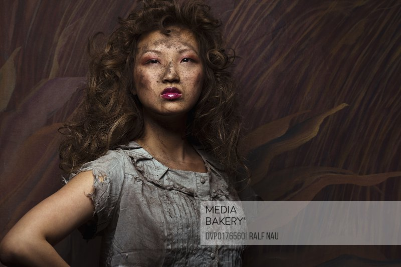 Beautiful Asian woman with mud and dirt on clothes and face