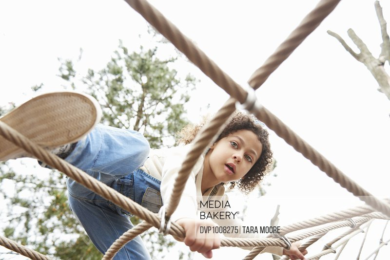 Young girl climbing on ropes in the playground