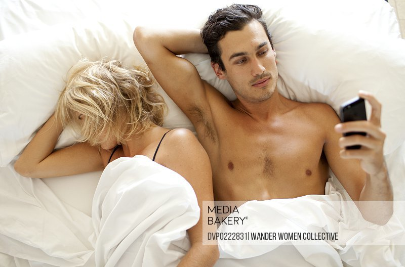 Man texting SMS on mobile phone in bed