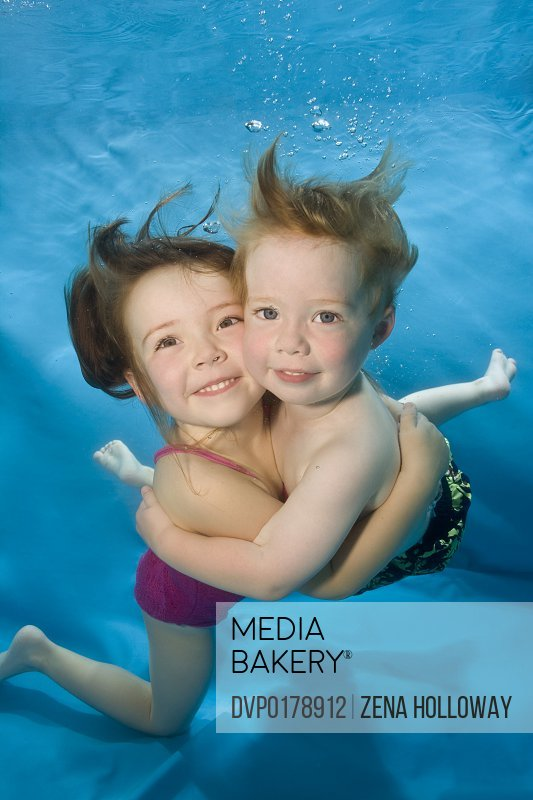 Brother and sister hugging underwater