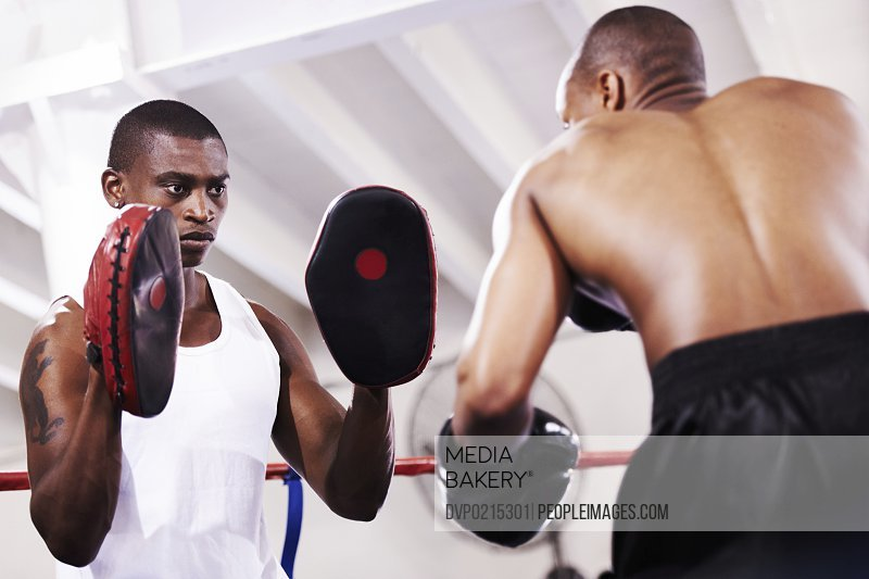 A boxer practicing with his sparring partner in the ring