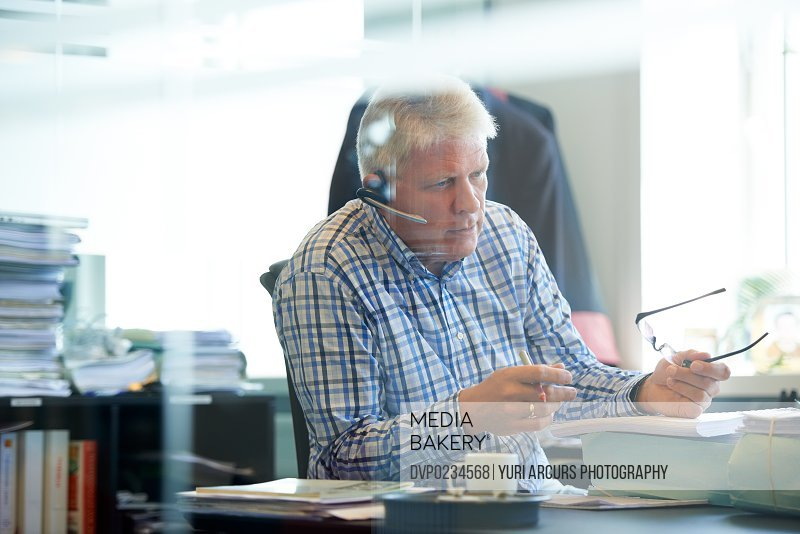 A senior businessman sitting in his office wearing a headset