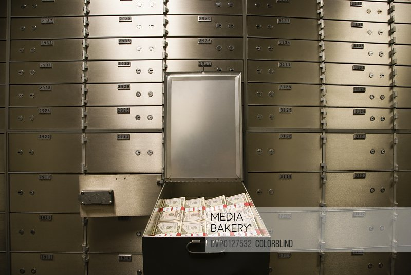 Open safety deposit box with cash inside