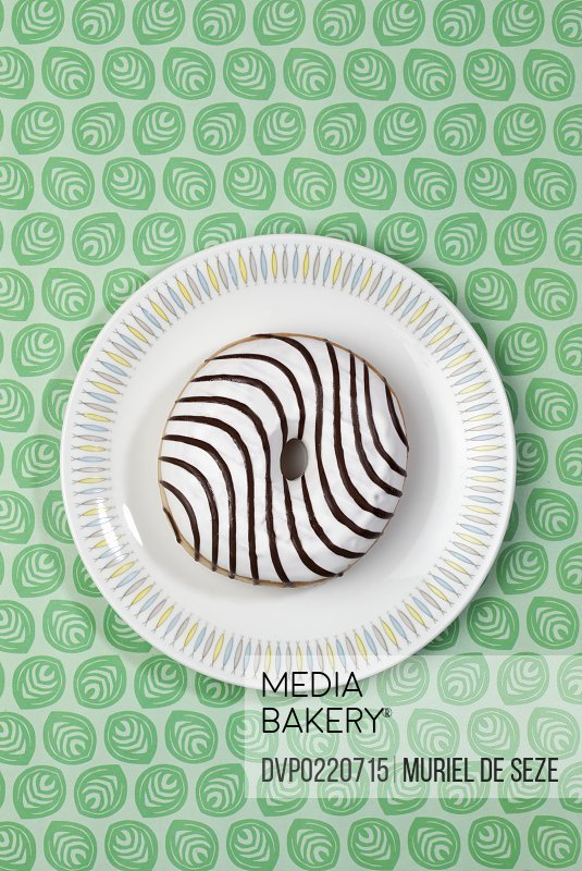 White donut with chocolate stripes.Green patterned table cloth.