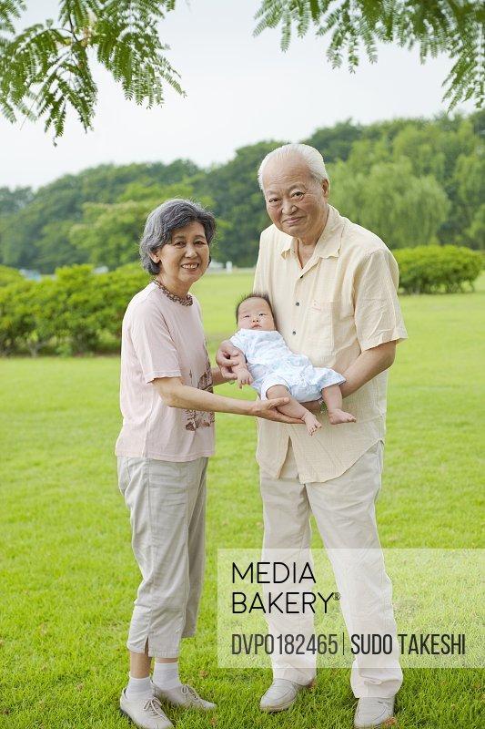Grandfather and grandmother that hug a grandchild