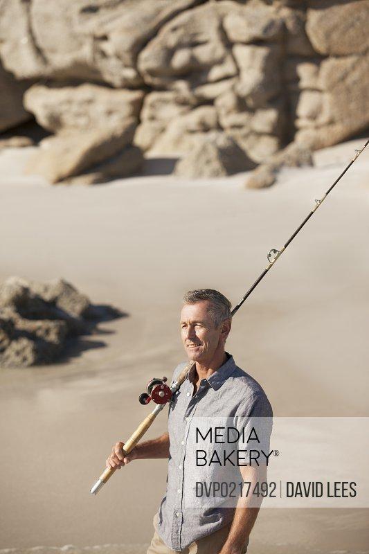 Mature man with fishing rod on beach