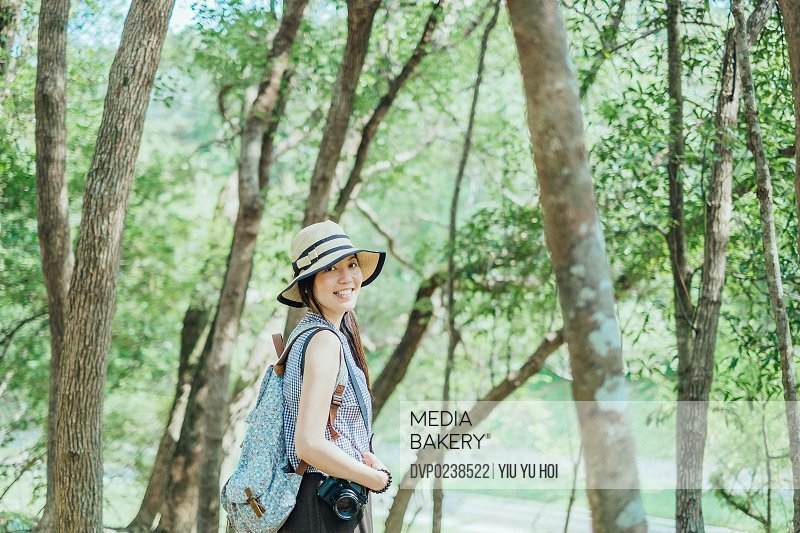 Portrait of a smiling young pretty female hiker with camera and backpack enjoying the calmness in the woods under the sun.