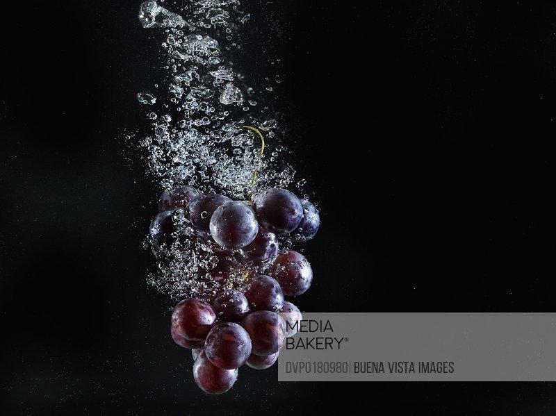 Grapes splashing in water