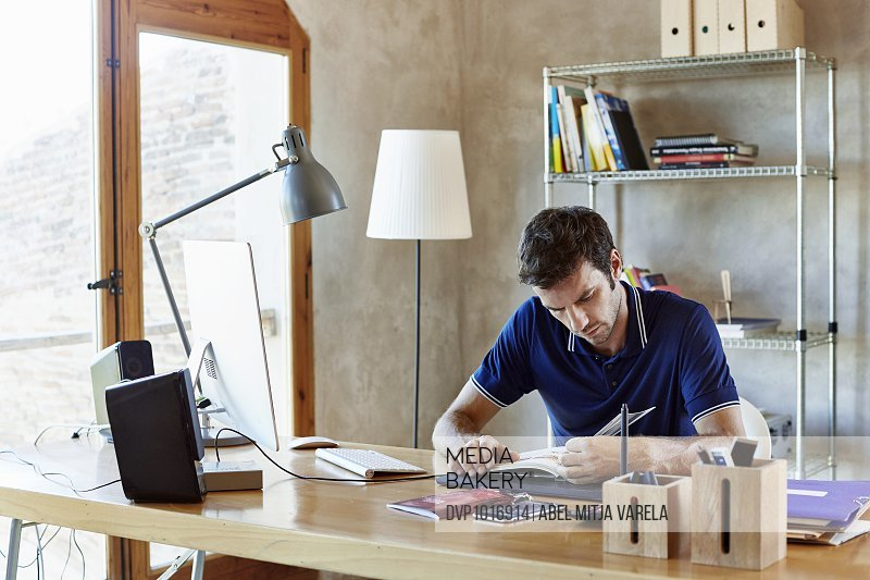 Businessman reading book in creative office