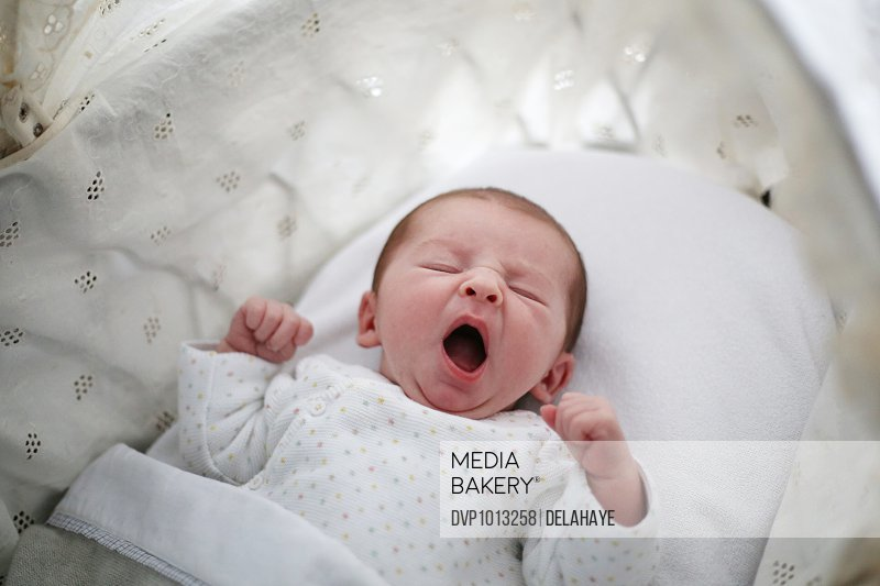 A new born baby girl yawning in her cradle