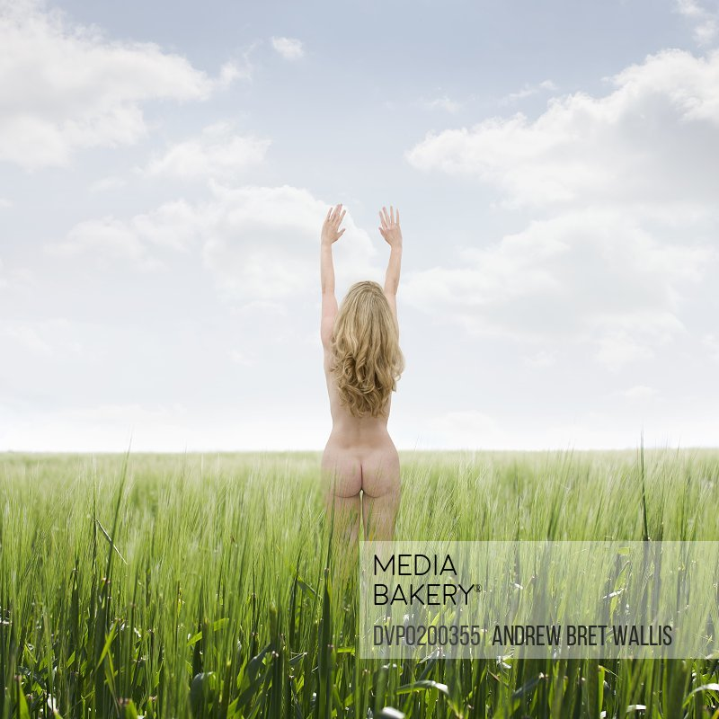 Nude woman with arms raised in a grass meadow