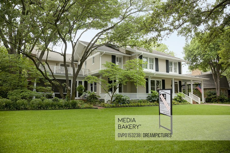 view of residential home with foreclosure sign sitting on the large green front lawn