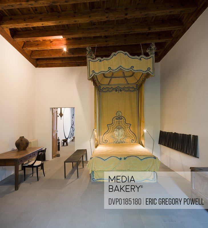 an antique silk bed in a large Tuscan loft apartment