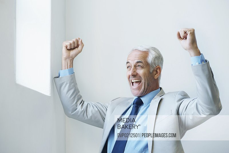 Shot of a mature businessman with his arms raised in victory