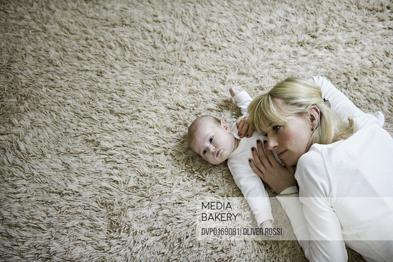 A mother is lying with her baby on the floor She is covering the baby's breast and stomach with her hands an head