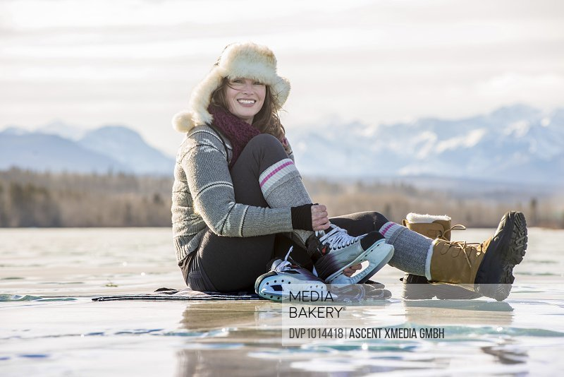 Young woman laces skates up on frozen pond