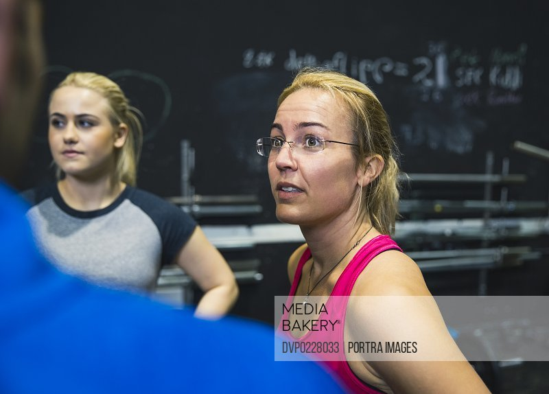 Female athlete communicating with friends in fitness club