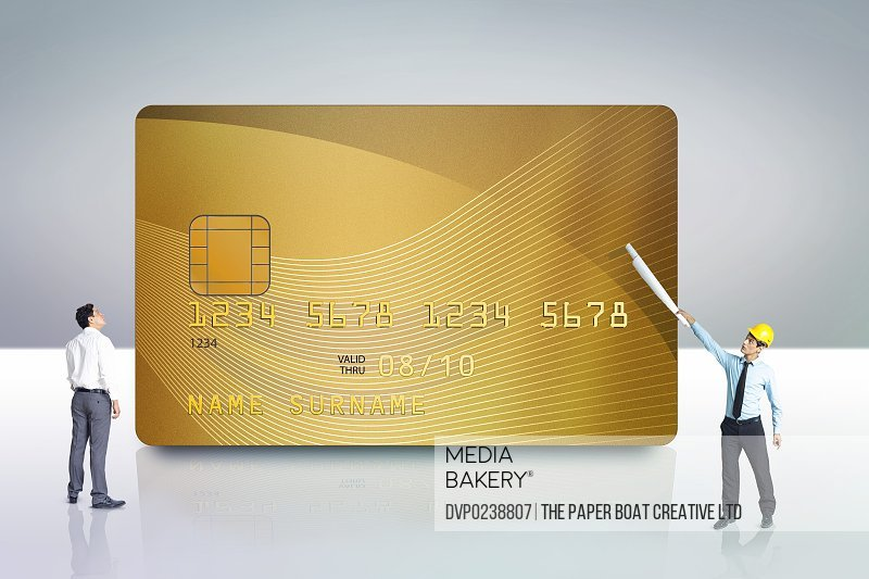Two men looking at a golden credit card