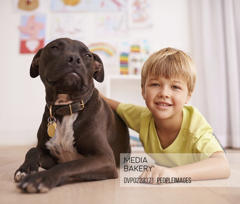 A little boy playing with his dog in his room