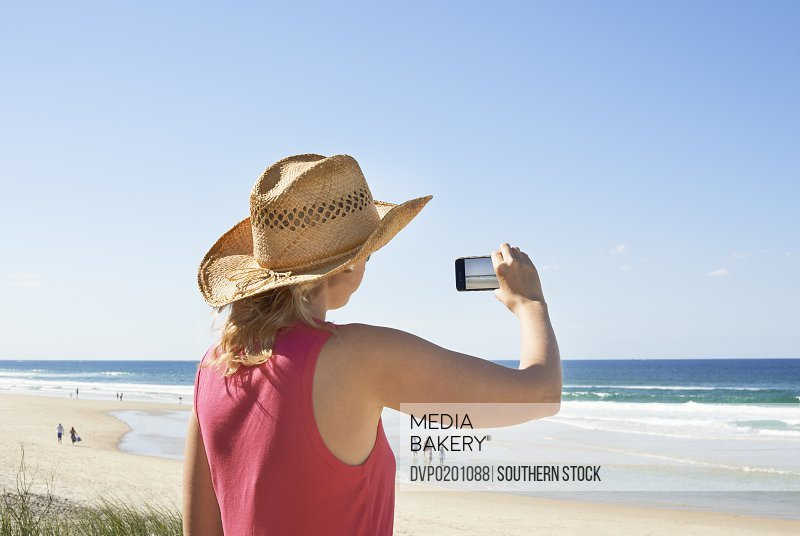 Woman in sun hat taking photos on cell phone.