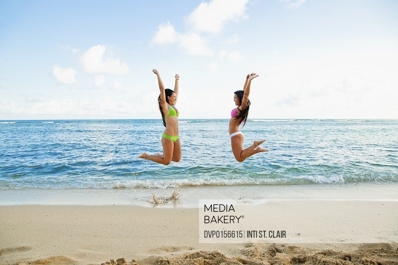 Two women jumping for joy on the beach