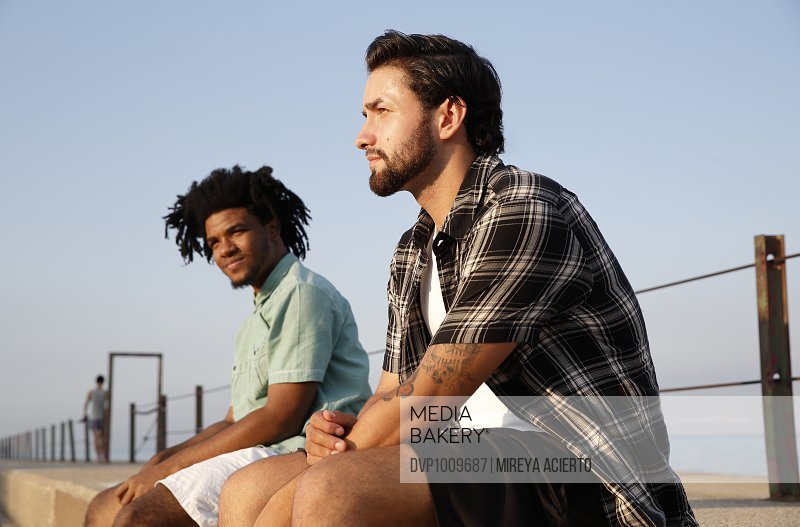 Two young ethnic men sit on the side of a pier during sunset.