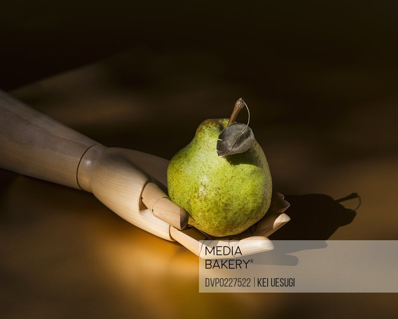 A pear in the wooden hand