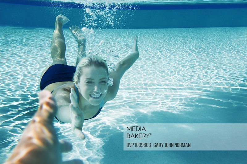 POV Happy young woman swimming underwater
