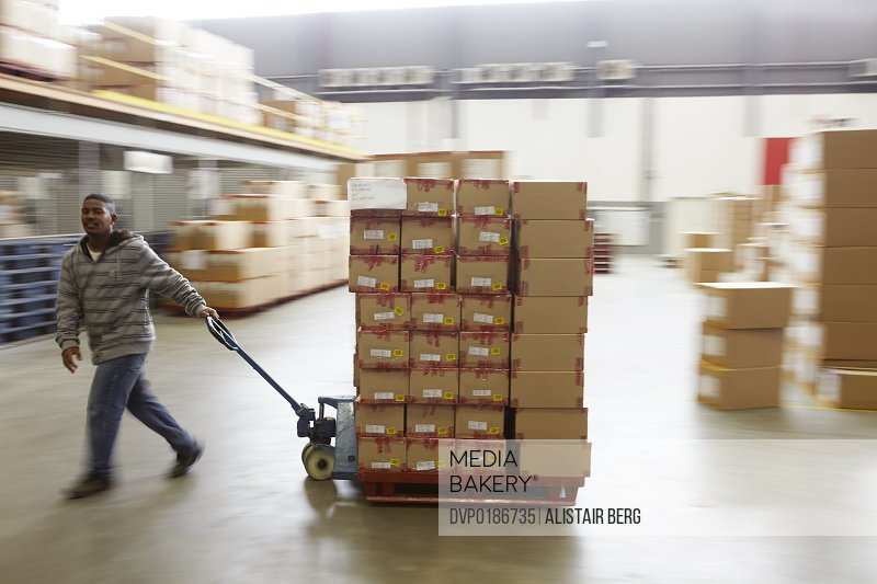 Worker moving boxes with a pallet truck inside a large distribution warehouse