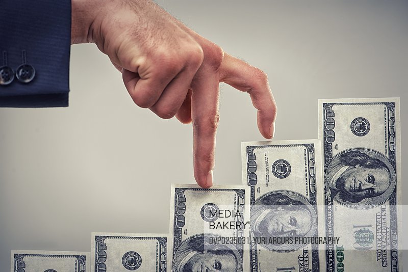 Close up concept shot of fingers walking crawling up a pile of one hundred dollar bills