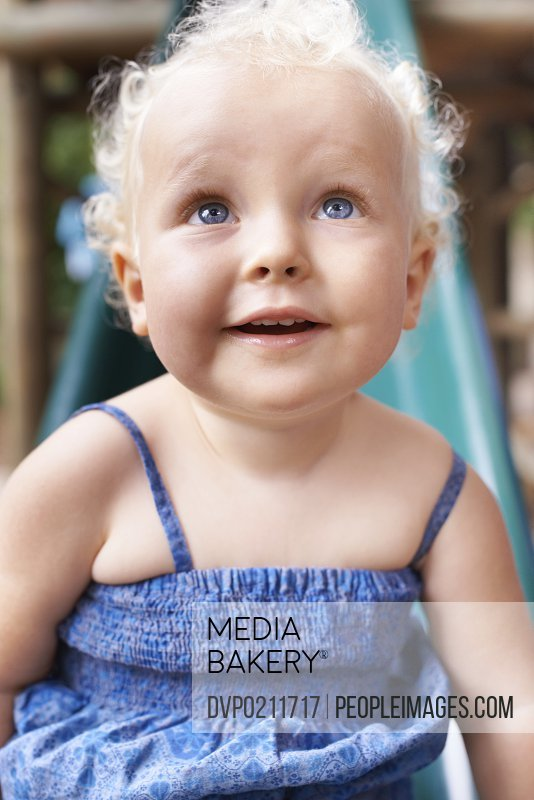 Closeup shot of an adorable baby girl with curly blond hair