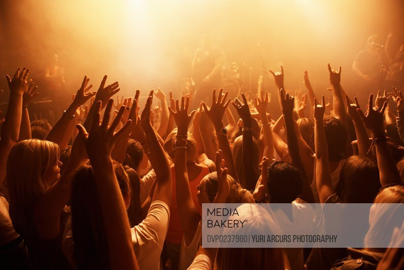 Rearview of a crowd at a music gig with their hands raised in the air