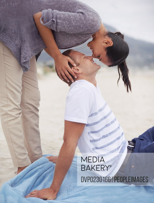 Shot of a young woman kissing her boyfriend on the beach