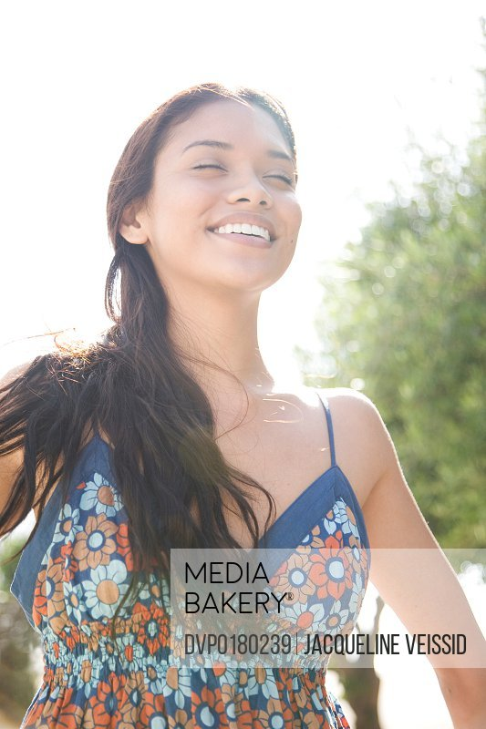 Cheerful woman backlit by the sun with eyes closed