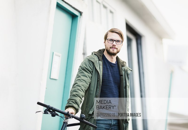 Portrait of confident young man with bicycle by building