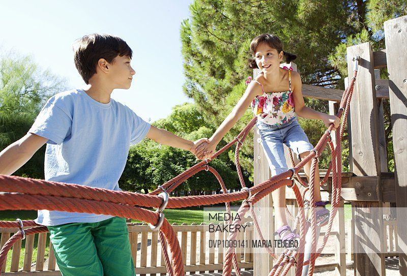 Child brother helping sister in playground ramp