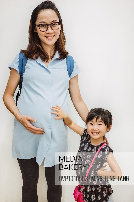 Pregnant mom & little daughter smiling at camera