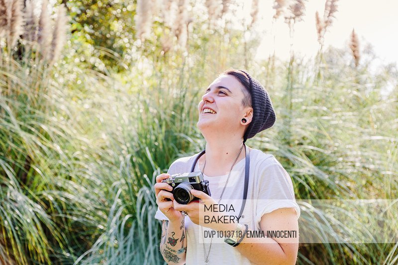 Young woman taking photo outdoor on sunny day