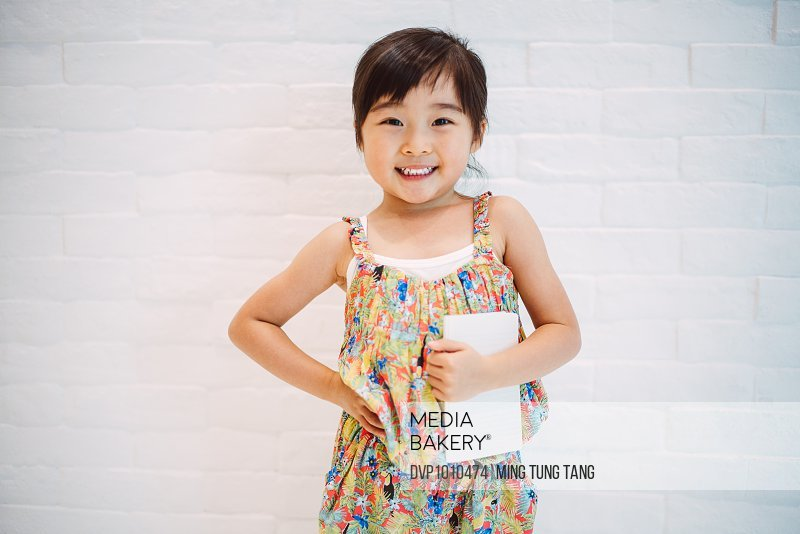 Little girl hold a note pad in front of white wall