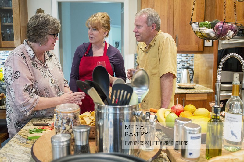 Three friends talking while preparing a meal