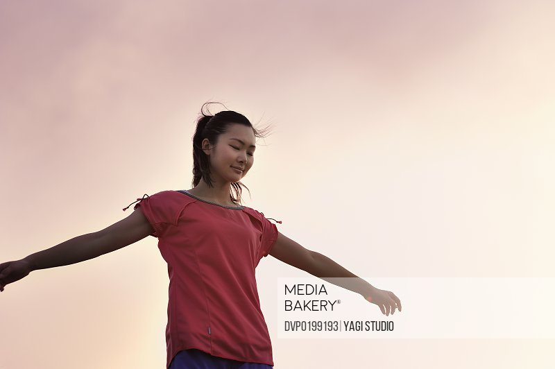 A woman standing wearing jogging wear at sunset