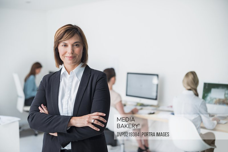 Female business leader with female team behind her