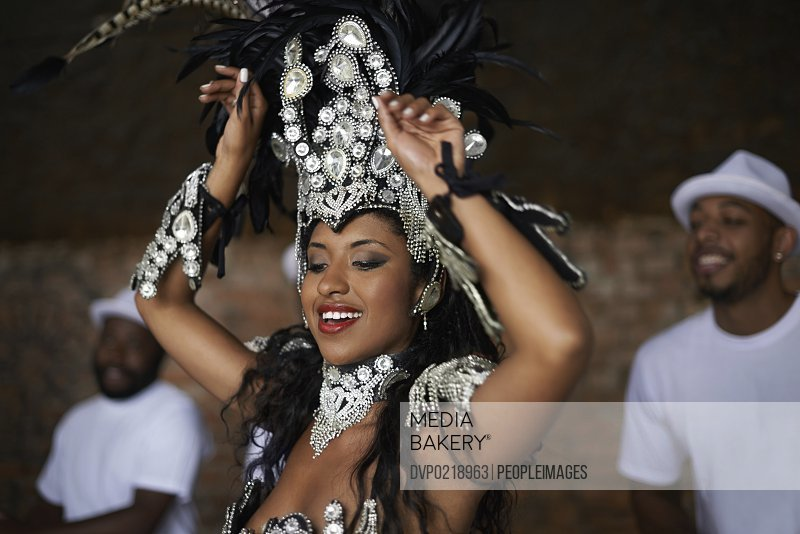 Shot of a beautiful samba dancer performing in a carnival with her band