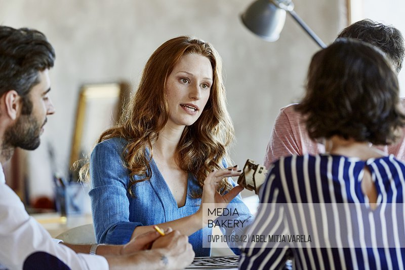 Businesswoman explaining model to colleagues