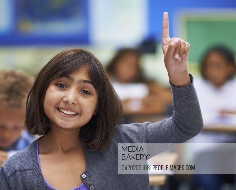 A little girl raising her hand in class